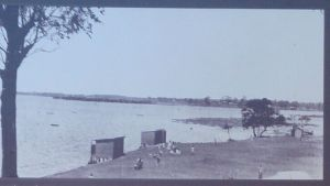 Locals and visitors enjoying a lazy day by the bay at Lota Camping Reserve in the 1930s.  You can see the iconic bathing boxes and a glimpse of the sandy shoreline.